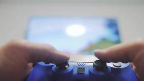 De kereljongen speelt op controlemechanismebedieningshendel gamepad de console Het spelen Videospelletjes online spelen Internet  stock video