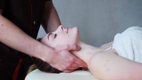 De kerelmasseur kneedt hals van jong meisje, dat op laag in heldere de kosmetiekruimte ligt stock video