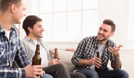 De kerels die bier drinken, die en vieren vergadering spreken royalty-vrije stock afbeelding