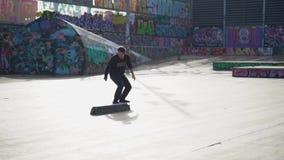 De kerels doet trucs op een skateboard in een vleetpark met graffiti wordt geschilderd die stock video