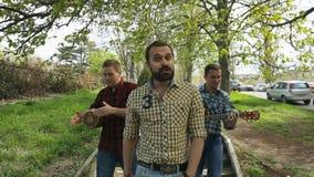 De kerels in plaidoverhemd die onderaan de straat lopen stock video