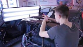 De kerelslagen met een hamer op de auto om de deuk op technologie PDR te richten De Reparatieverwijdering van de Paintlessdeuk we stock videobeelden