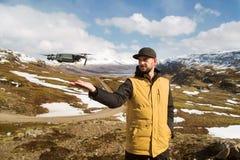 De kereltoerist lanceert quadrocopter met indient de bergen stock afbeelding