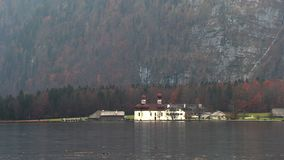 De kerk bevindt zich op het meer in de bergen van Beieren stock videobeelden