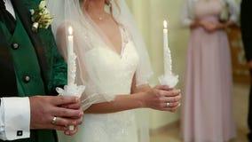 De kerk, de bruid en de bruidegom houden kaarsen op het huwelijk stock videobeelden