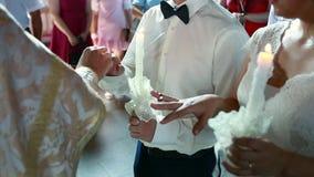De kerk, de bruid en de bruidegom houden kaarsen op het huwelijk stock footage