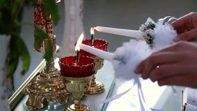 De kerk, de bruid en de bruidegom houden kaarsen op het huwelijk stock video