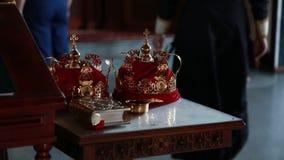De kerk, priester neemt de gouden kroon aan zijn handen stock video
