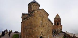 De Kerk van de Gergetidrievuldigheid of Heilige Drievuldigheidskerk dichtbij het dorp van Gergeti in Georgië royalty-vrije stock foto's