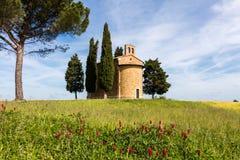 De kerk van Toscanië door cipressen wordt omringd die Royalty-vrije Stock Afbeelding