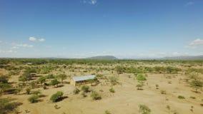 De kerkbouw in midden van enorm Afrikaans savannelandschap op hete dag stock video