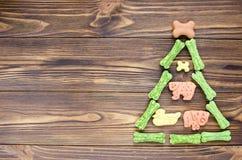De kerstboom maden van honds het kauwen beenderen en koekjes op wo royalty-vrije stock afbeelding
