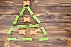 De kerstboom maden van honds het kauwen beenderen en koekjes op wo stock afbeelding