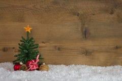 De kerstboom met stelt op een houten achtergrond met sneeuw voor stock afbeeldingen
