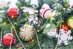 De Kerstboom op de straat is verfraaid met diverse heldere speelgoed en sneeuwvlokken stock afbeelding