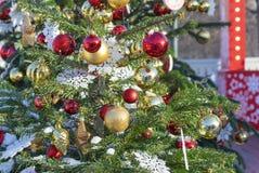 De Kerstboom is verfraaid met gouden en rode ballen en witte sneeuwvlokken stock fotografie