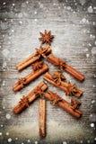 De kerstkaart met Kerstmisspar maakte van kruidenpijpjes kaneel, anijsplantster en rietsuiker op rustieke houten achtergrond, ma Stock Afbeeldingen