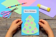 De Kerstkaart van de kindholding in zijn handen Document groetkaart met tekst Vrolijke Kerstmis en Kerstboom met ornamenten Royalty-vrije Stock Afbeeldingen