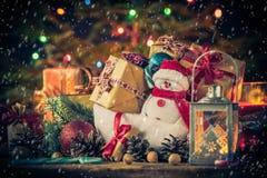 De kerstkaartsneeuwman siert de lichtenachtergrond van de giftenboom Stock Foto