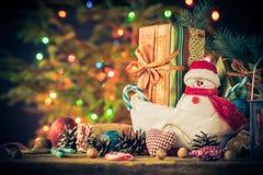 De kerstkaartsneeuwman siert de lichtenachtergrond van de giftenboom Stock Afbeelding