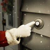 De kerstman belt een deurklok Stock Foto's