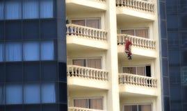 De Kerstman die een gebouw in Kerstmis beklimt Royalty-vrije Stock Afbeeldingen