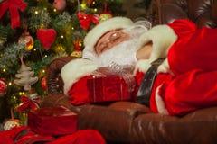 De Kerstman die in een verfraaide woonkamer met zakhoogtepunt dutten stock foto's