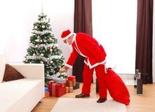 De Kerstman die gift zet onder Kerstmisboom Stock Foto