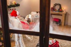 De Kerstman die giftdozen thuis bekijken in woonkamer Royalty-vrije Stock Fotografie
