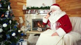 De kerstman die op cellphone, vakantievoorbereiding, heilige Nicolas spreken houdt van cellulair, de Kerstman stock video