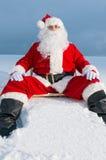 De kerstman die sunbed in sneeuw zitten Stock Foto