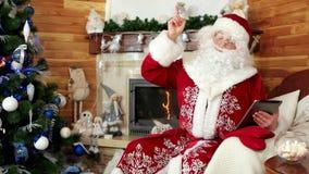 De kerstman die tablet, het kiezen van de Kerstman gebruiken stelt met behulp van gadget, nieuwe ideeën, open haard voor stock video