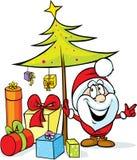 De Kerstman die zich door Kerstmisboom bevinden Stock Foto's