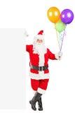 De Kerstman die zich naast een aanplakbord bevindt Stock Foto