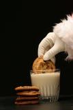 De kerstman dompelt een koekje in de melk onder Royalty-vrije Stock Foto's