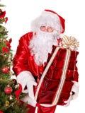 De Kerstman door Kerstmisboom. Stock Foto