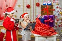 De kerstman en de helper verhalen gelukkig giften in een zak en gecontroleerd tegen de lijst stock afbeeldingen