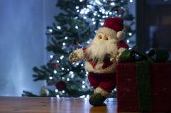 De Kerstman en heldere rode giftdoos en Kerstmisboom op achtergrond royalty-vrije stock afbeeldingen
