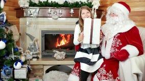 De kerstman geeft meisjesgift, gelukkig glimlachend kind, komen de wensen ware, nieuwe jaar en Kerstmisviering stock videobeelden