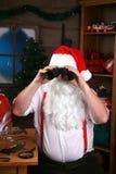 De kerstman kijkt door zijn verrekijkers Stock Foto