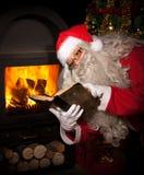 De Kerstman leest een boek Stock Afbeeldingen