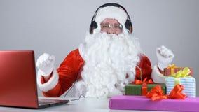 De Kerstman luistert aan muziek op hoofdtelefoons en danst 50 fps stock videobeelden