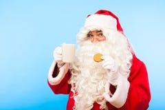 De Kerstman met een kop van koffie of thee en een koekje op blauwe bedelaars Royalty-vrije Stock Foto