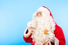 De Kerstman met een kop van koffie of thee en een koekje op blauwe bedelaars Royalty-vrije Stock Fotografie