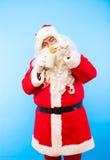 De Kerstman met een kop van koffie of thee en een koekje op blauwe bedelaars Royalty-vrije Stock Afbeelding