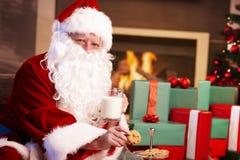 De Kerstman met melk en chocoladeschilferkoekjes Stock Foto