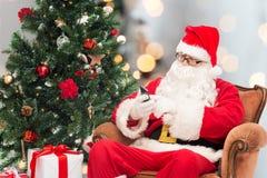 De Kerstman met smartphone en Kerstmisboom stock foto