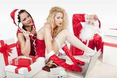 De Kerstman met twee sexy helpers in zijn bureau Stock Afbeeldingen