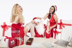 De Kerstman met twee sexy helpers in zijn bureau Royalty-vrije Stock Foto