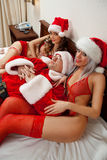 De Kerstman met twee sexy meisjes stock foto